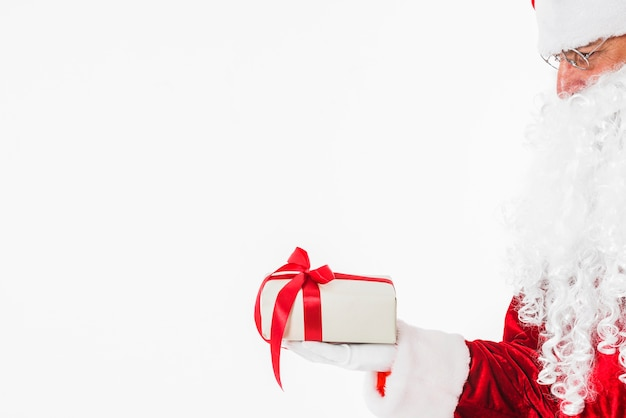 Santa claus in glasses holding gift box Free Photo