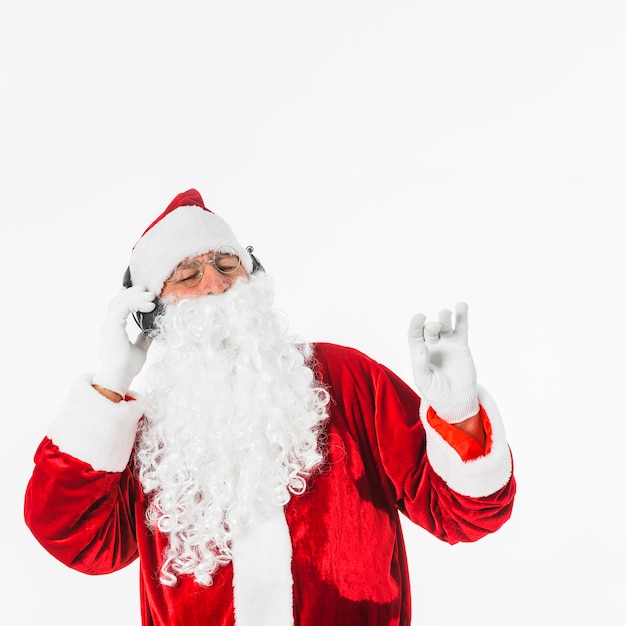 Santa claus in glasses listening to music with headphones Free Photo
