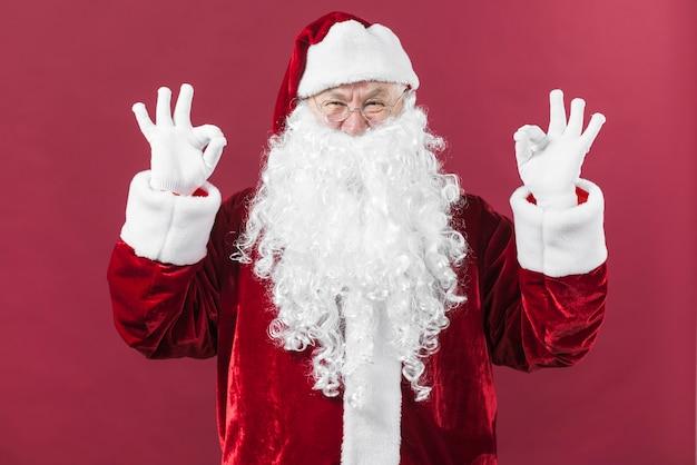 Santa claus in glasses showing okay gestures Free Photo