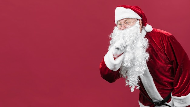 Santa claus in glasses showing secret gesture Free Photo
