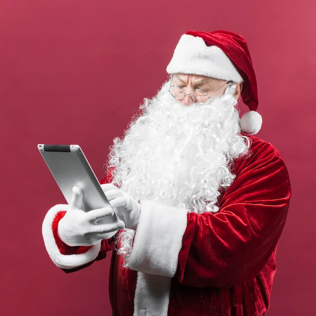 Santa claus in glasses using tablet Free Photo