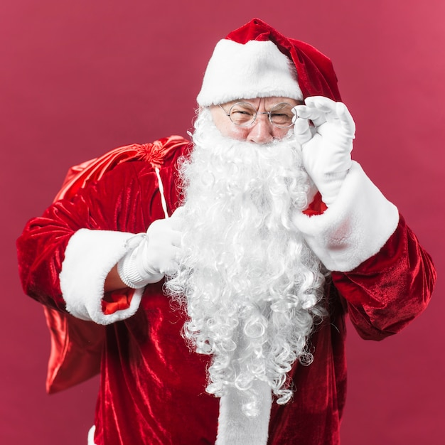 Santa claus in glasses with sack behind back Free Photo