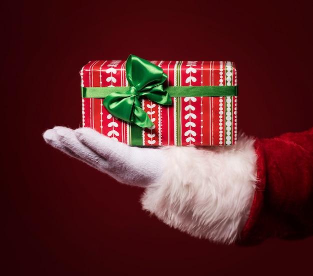 빨간색 배경에 선물 상자를 들고 산타 클로스 손 무료 사진