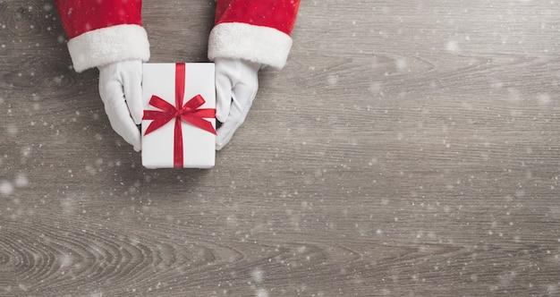 Санта-клаус руки держит белую подарочную коробку с красной лентой Premium Фотографии