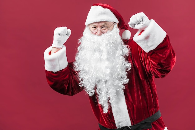 Santa claus in hat showing fists Free Photo