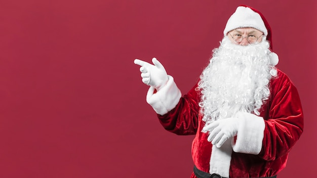 Santa claus in hat with pointing hand Free Photo