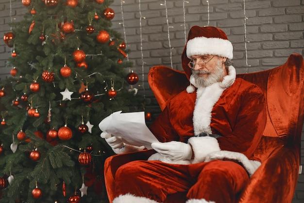Дед мороз отдыхает у елки. украшение дома. санта с письмом от детей. Бесплатные Фотографии