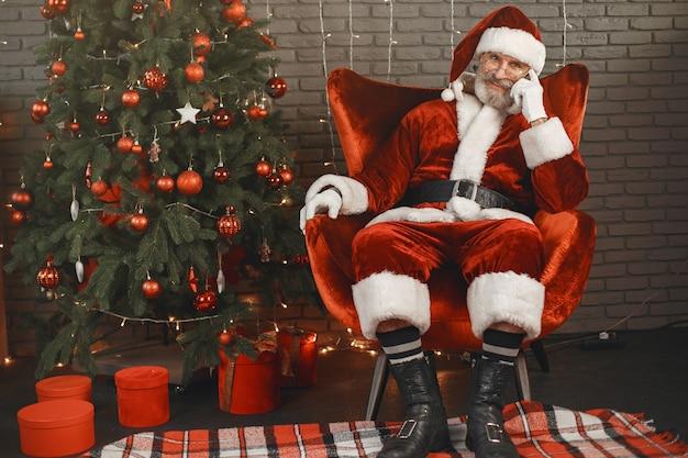 Дед мороз отдыхает у новогодней елки. украшение дома. Бесплатные Фотографии