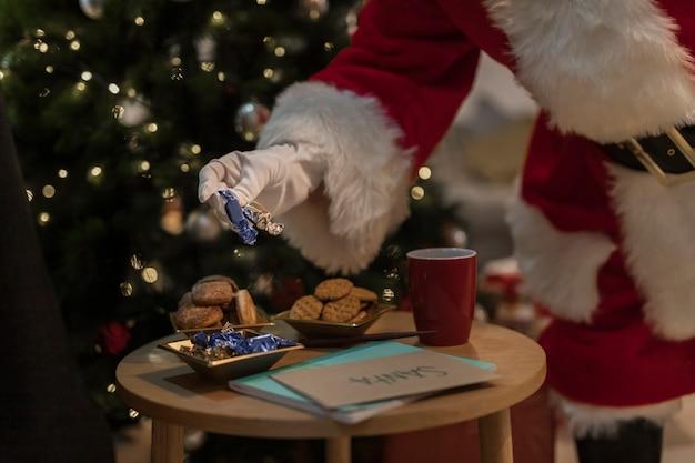 Santa claus having christmas cookies Free Photo
