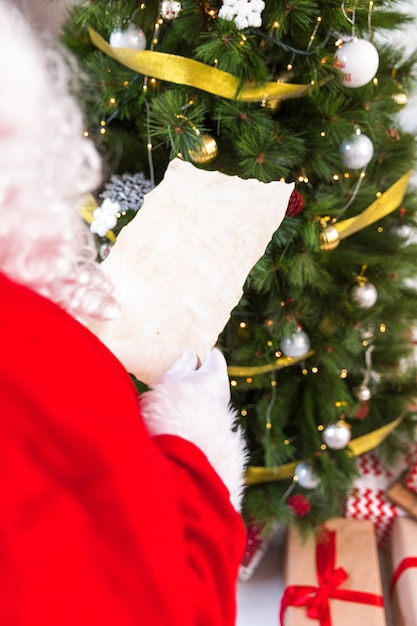 Santa claus holding empty wish list Free Photo