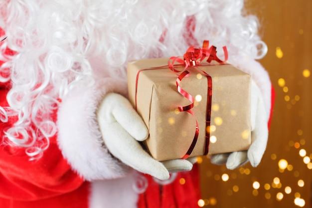 Санта-клаус держит подарочную коробку против размытых рождественских огней Premium Фотографии