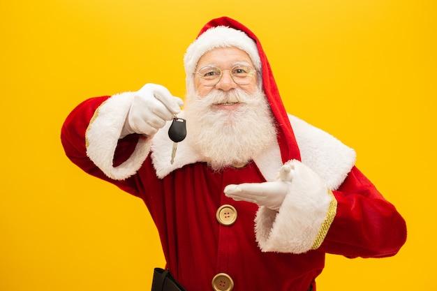 Santa claus holding keys of a car on yellow background. Premium Photo