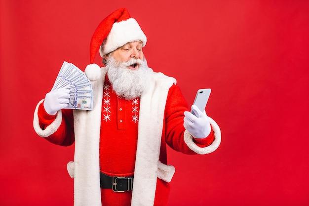 Santa claus holding money and using phone Premium Photo