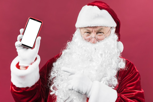 Santa claus holding phone in hand Free Photo