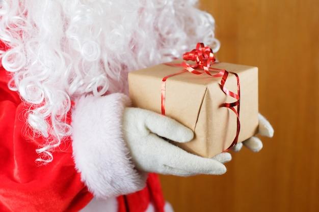 Санта-клаус в белых перчатках и белая борода, холдинг подарочной коробке. Premium Фотографии