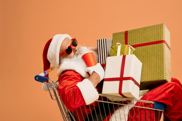 Santa claus inside shopping cart with lots of gift boxes Premium Photo