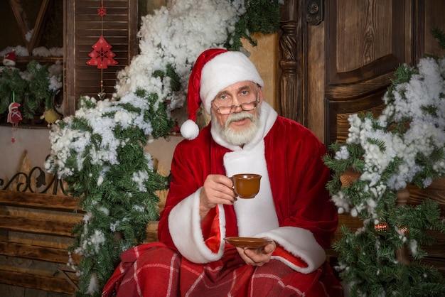 サンタクロースは熱いお茶やコーヒーを飲んでいます。 Premium写真