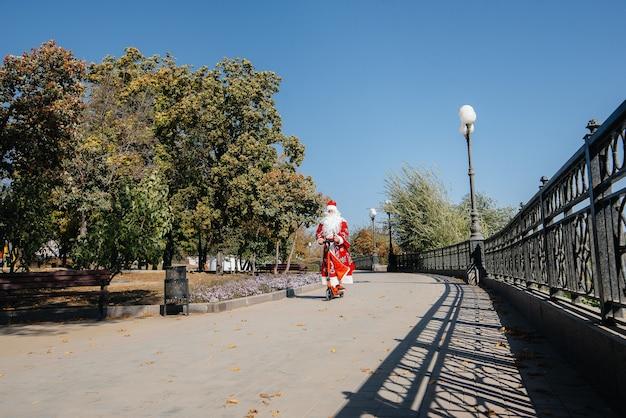 Дед мороз спешит на самокате с подарками к празднику детям. Premium Фотографии