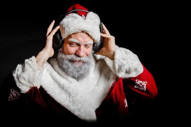 Santa claus is listening to music with headphones on a black background Premium Photo