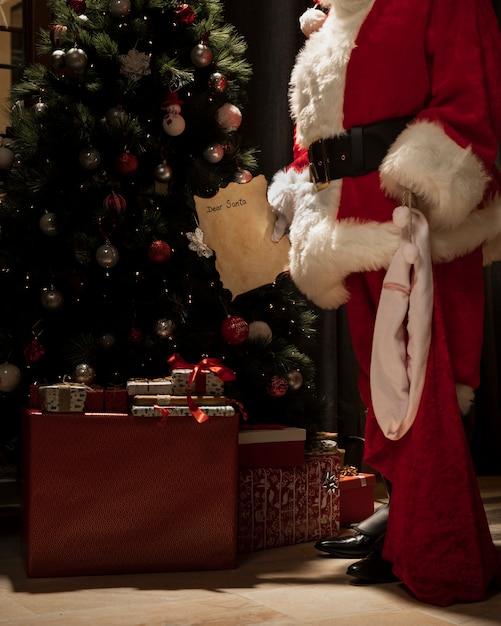 Santa claus leaving christmas presents Free Photo