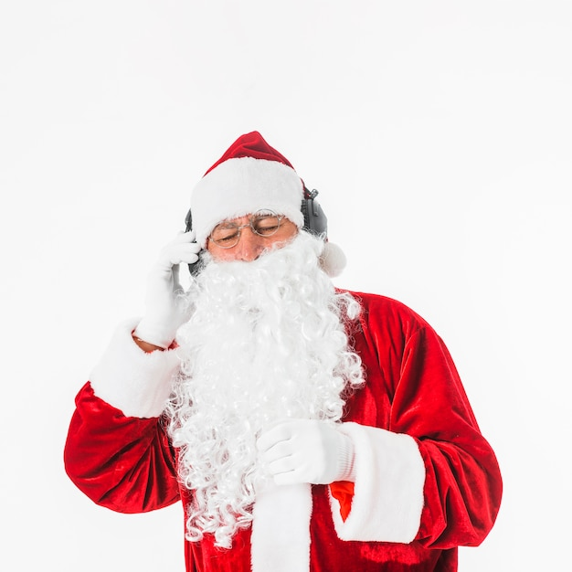 Santa claus listening to music with headphones Free Photo