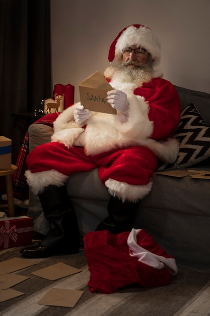 Santa claus opening a letter from a kid Free Photo