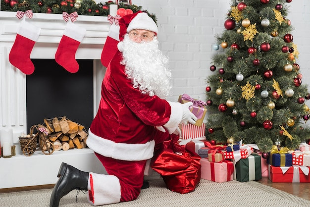 Santa claus putting presents under christmas tree Free Photo