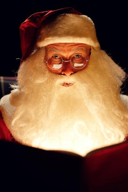 暗い部屋に座って魔法の本を読んでいるサンタクロース Premium写真