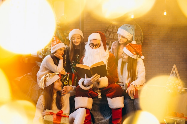 Santa claus reading a book to a group of kids Free Photo