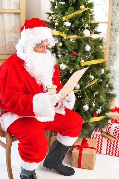 Santa claus reading paper near christmas tree Free Photo