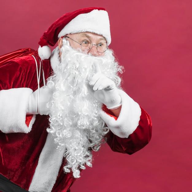 Santa claus in red hat showing secret gesture Free Photo