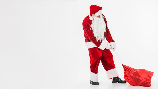 Santa claus in red pulling sack of gifts Free Photo