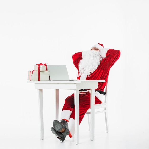 Santa claus resting on chair at table Free Photo