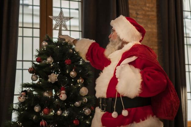 Santa claus setting up christmas tree Free Photo