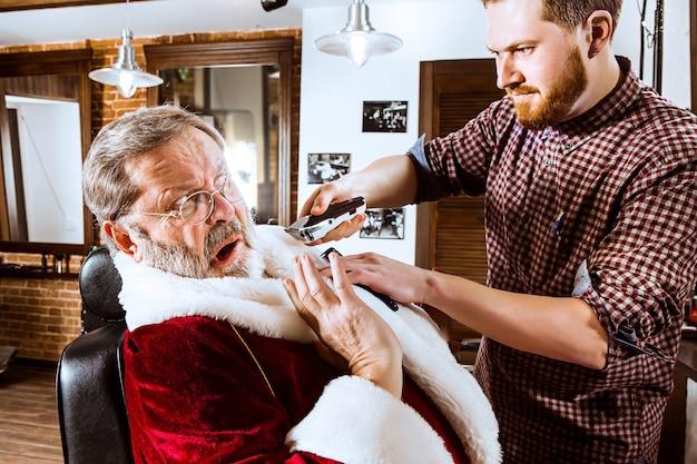 Babbo natale che rade il suo barbiere personale Foto Gratuite