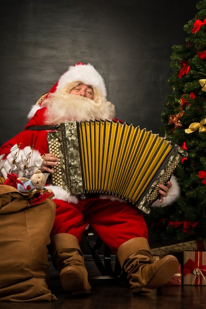 Santa claus sitting in armchair near christmas tree at home and playing music on accordion Premium Photo