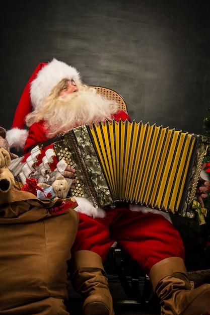 Santa claus sitting in armchair playing music on accordion Premium Photo
