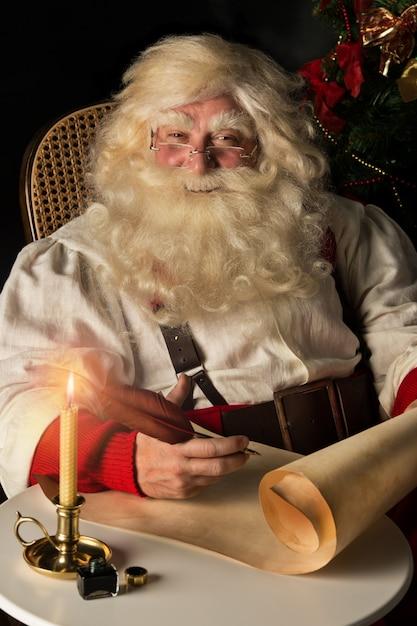 산타 클로스 집에 앉아서 퀼 펜으로 목록을 작성하는 오래 된 종이 롤에 쓰기 프리미엄 사진