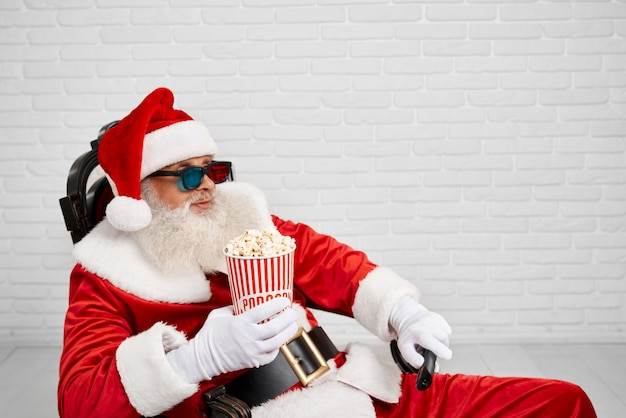 Santa claus sitting in chair with popcorn and tv zapper Premium Photo