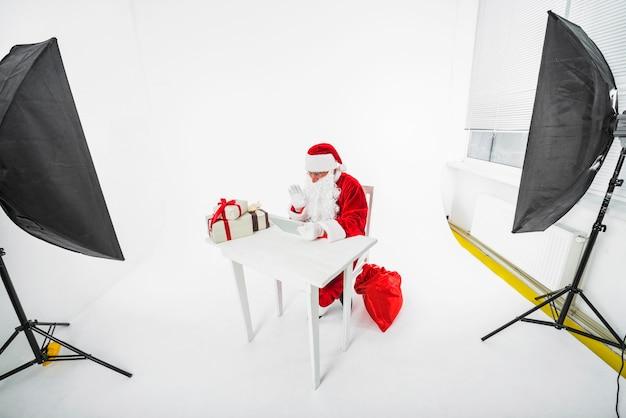 Santa claus sitting at table in photo studio Free Photo