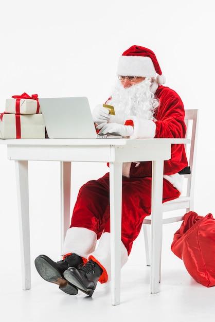 Santa claus sitting at table with credit card Free Photo