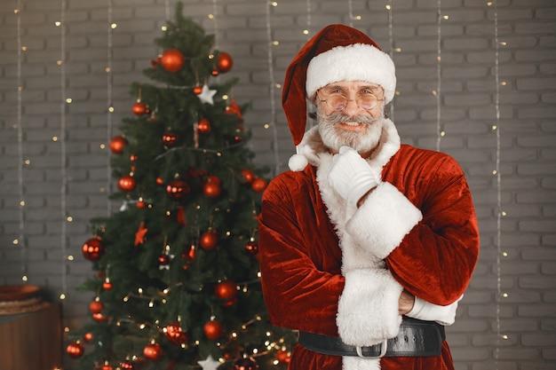 Санта-клаус стоит у елки рождества. украшение дома. Бесплатные Фотографии