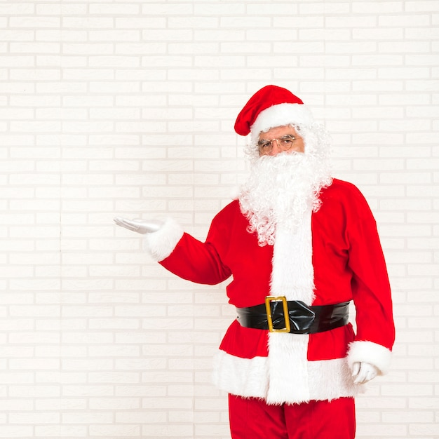 Santa claus standing with outstretched hand Free Photo