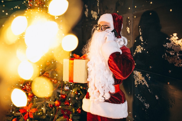 Santa claus talking on the phone and holding a present Free Photo
