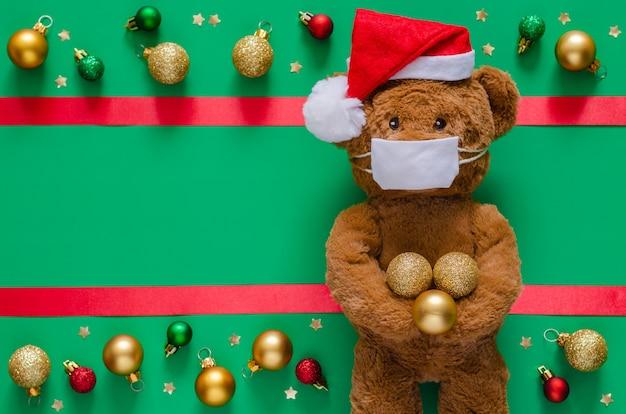 Санта-клаус плюшевый мишка в маске на размытом зеленом с украшениями. Premium Фотографии