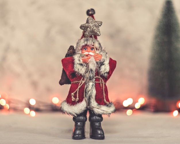 Santa claus toy holds a staff with a star and a christmas tree on a background Premium Photo