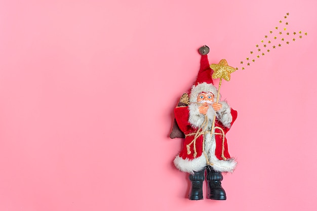 Santa claus toy holds a staff with star on pink background concept happy new year flat lay Premium Photo