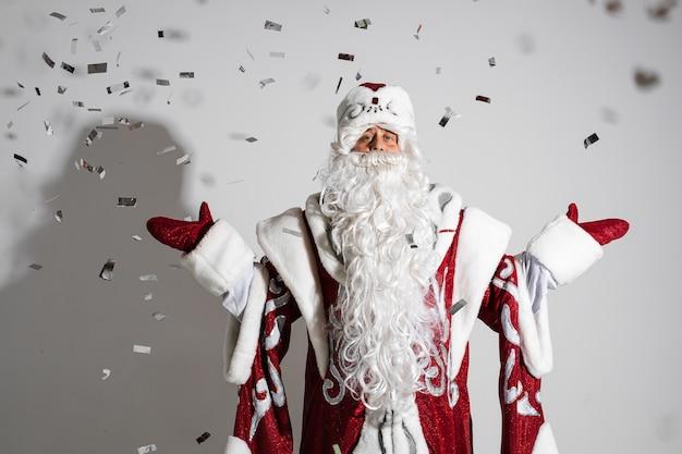 Санта-клаус под праздничным рождественским конфетти показывает приветственный жест Бесплатные Фотографии