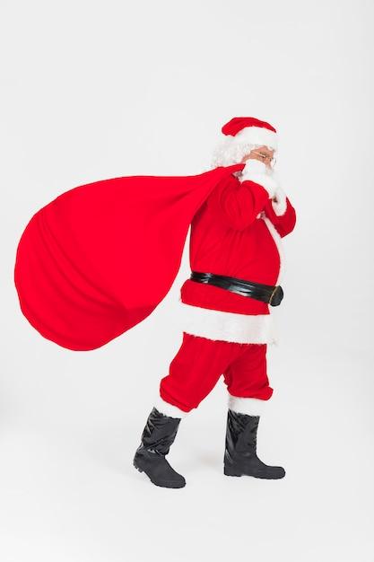 Санта-клаус идет с мешком подарков Premium Фотографии
