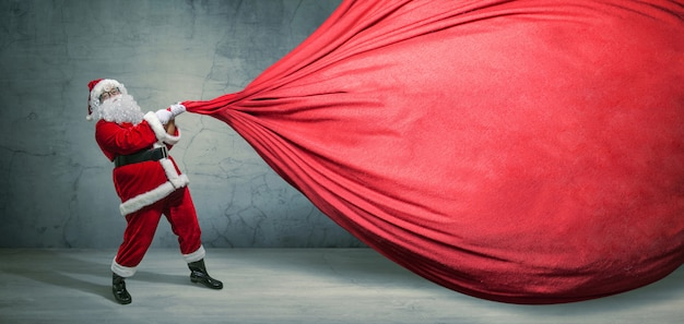 Santa claus with big bag on blank advertisement banner with copy space Premium Photo